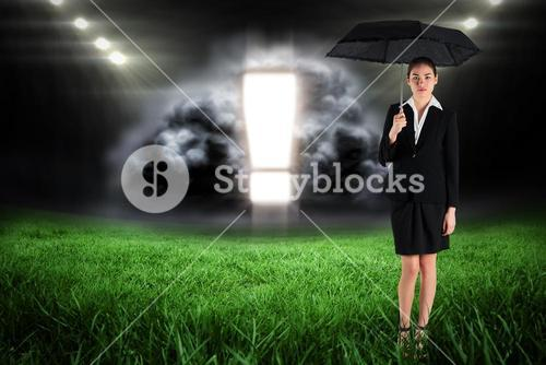 Composite image of young businesswoman holding umbrella