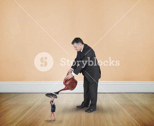 Composite image of mature businessman watering tiny businesswoman