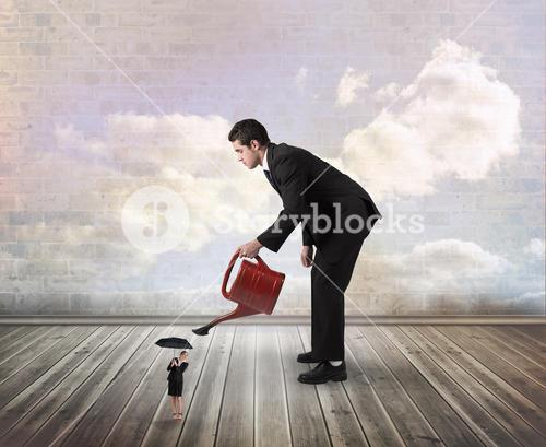 Composite image of businessman watering tiny businesswoman