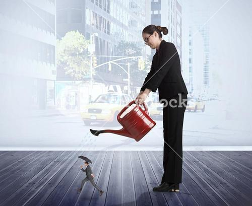 Composite image of businesswoman watering tiny businessman