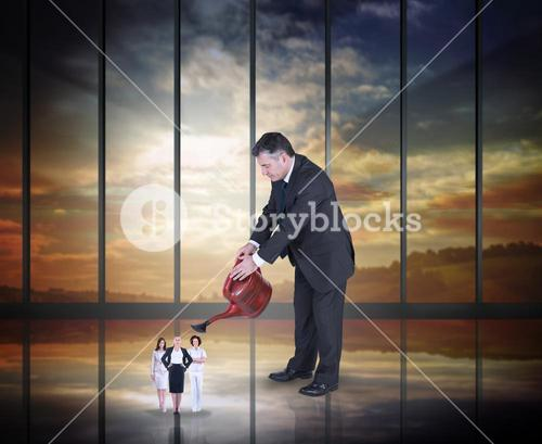 Composite image of mature businessman watering tiny business women