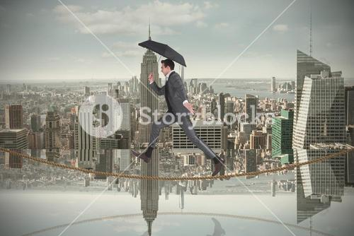 Composite image of businessman jumping on tightrope holding an umbrella