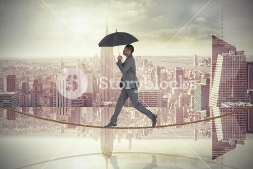 Composite image of businessman walking on tightrope and holding umbrella