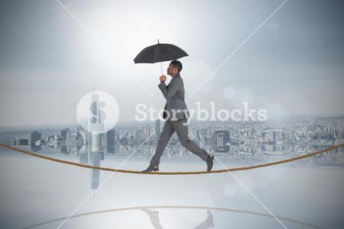 Composite image of businessman walking and holding umbrella on tightrope
