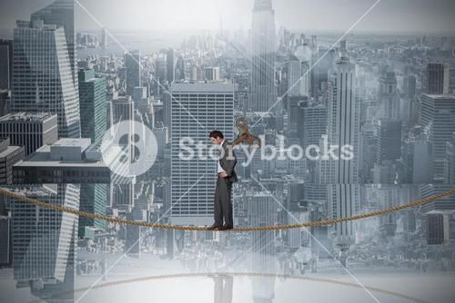 Composite image of wound up businessman with hands on hips on tightrope