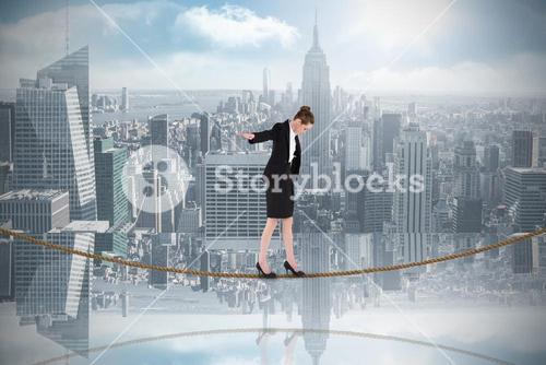 Composite image of businesswoman performing a balancing act on tightrope