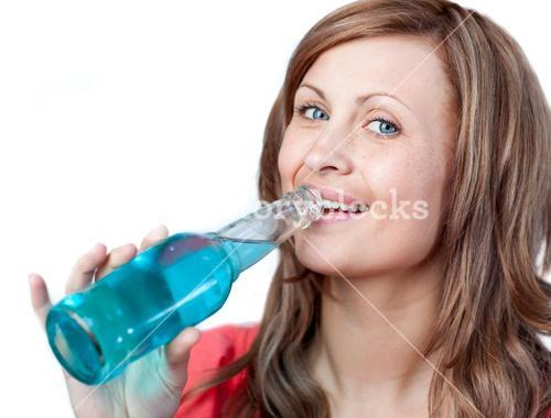 Happy woman drinking a blue beverage