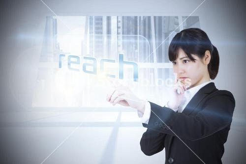 Businesswoman pointing to word reach