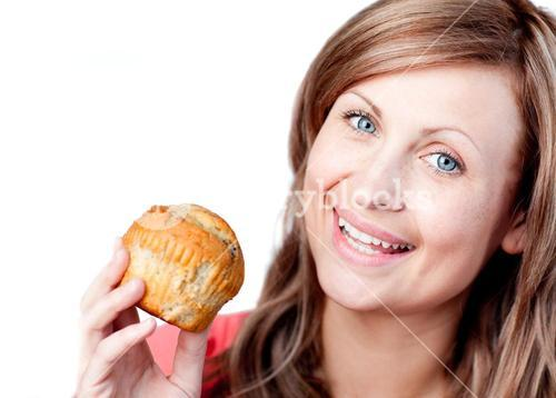 Cheerful woman is eating a cake