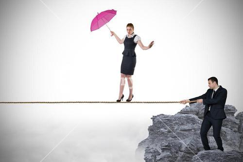 Young businessman pulling a tightrope for businesswoman