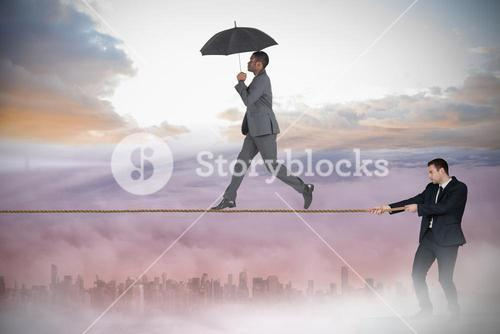 Young businessman pulling a tightrope for business man