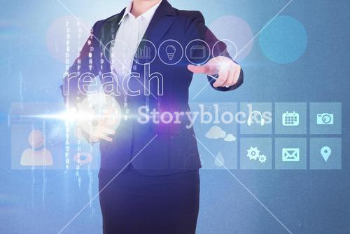 Businesswoman touching the word reach on interface