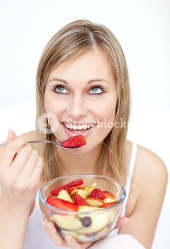 Jolly woman eating fruit salad