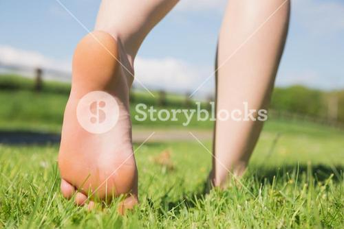 Womans feet walking away on grass