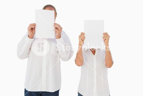 Couple holding paper over their faces