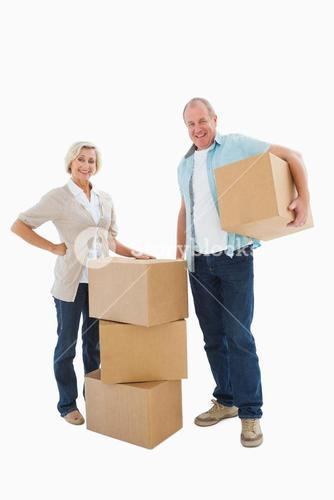 Older couple smiling at camera with moving boxes
