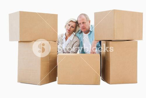 Stressed older couple with moving boxes