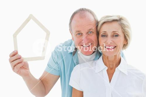 Happy older couple holding house shape