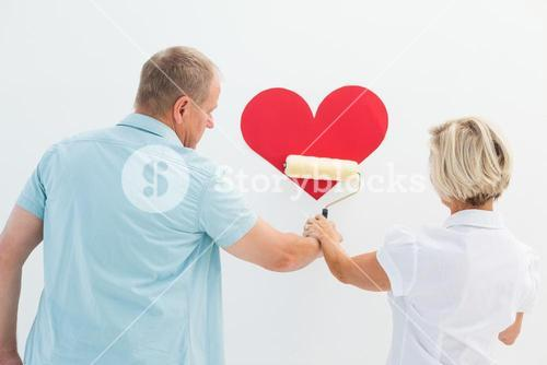 Happy older couple painting red heart