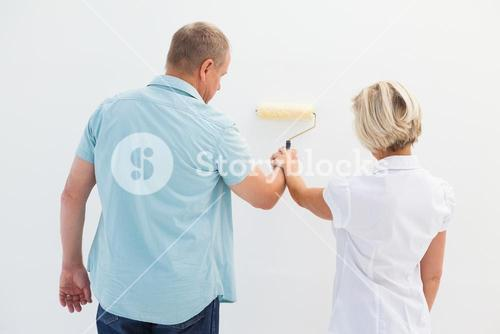 Happy older couple painting white wall