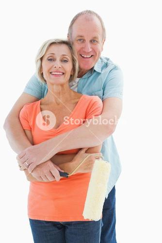 Happy older couple holding paint roller