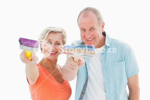 Happy older couple holding paintbrushes