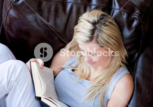Joyful woman reading a book on a sofa