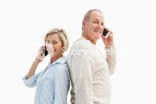 Happy mature couple talking on their phones