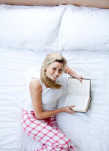 Delighted woman reading a book on a bed