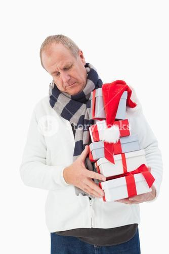 Mature man in winter clothes holding gifts