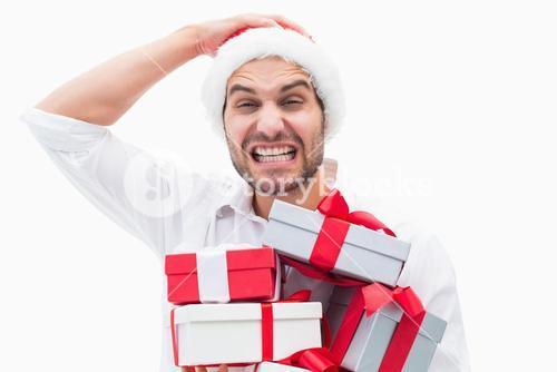 Stressed festive man holding gifts