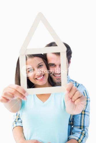 Happy young couple with house shape