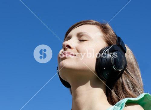 Cute woman is listening music outdoor