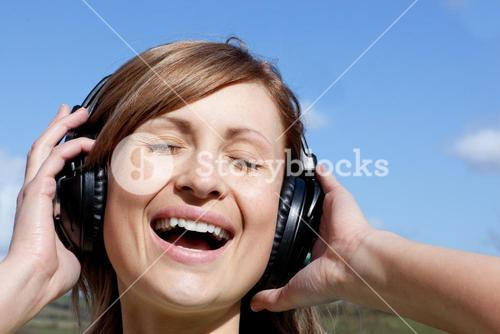 Joyful woman is listening music outdoor