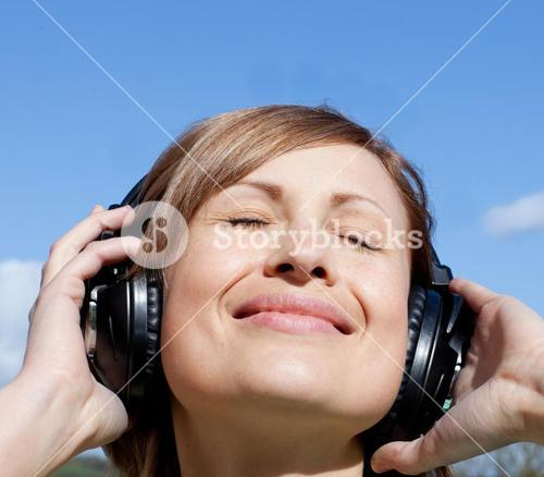 Happy woman is listening music outdoor