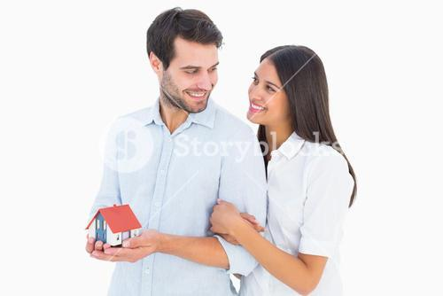Attractive young couple holding a model house