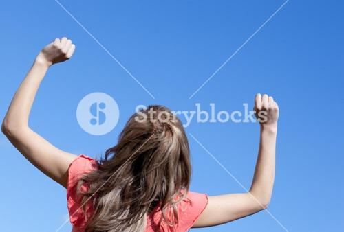 Smiling woman punching the air outdoor