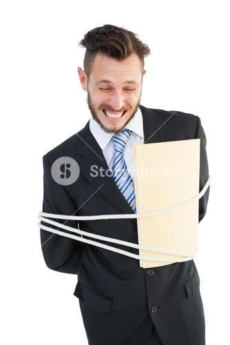 Serious businessman tied up at work