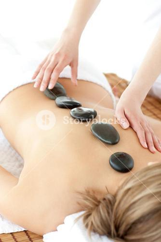 Cute woman having a stone therapy against a white background