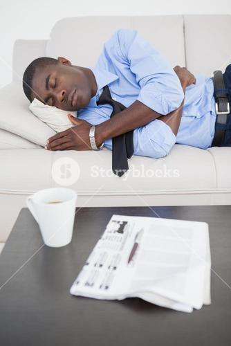 Tired businessman sleeping on the sofa