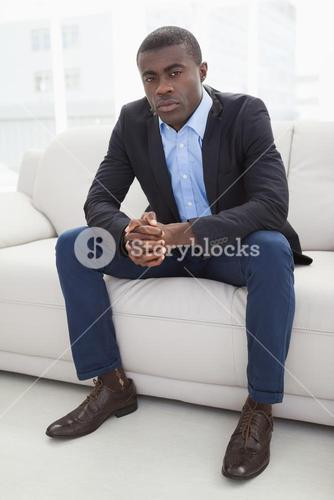 Serious businessman looking at camera on couch