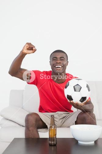 Football fan sitting on couch with ball cheering