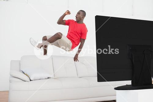Football fan jumping over couch cheering