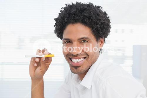 Happy businessman holding electronic cigarette