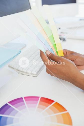 Designer working at desk holding colour samples