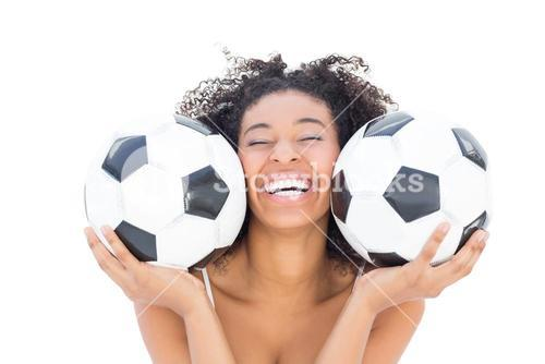 Pretty girl with afro hairstyle smiling at camera holding footballs