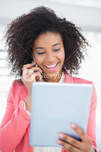 Casual businesswoman talking on phone holding tablet pc