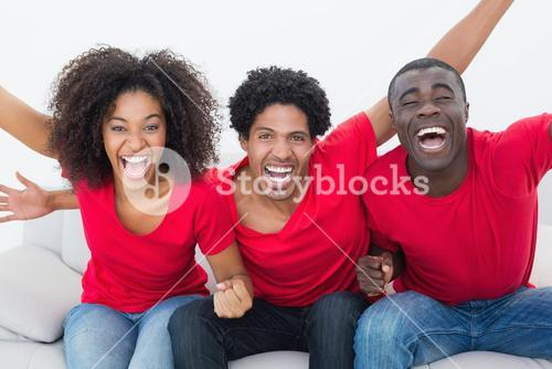 Football fans in red sitting on couch cheering