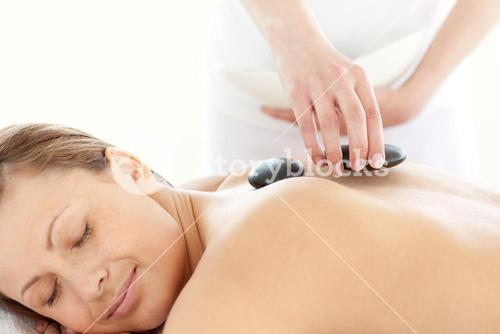 Portrait of a radiant woman having a massage with stones