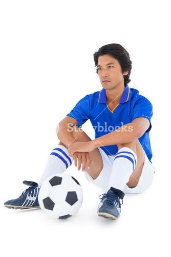 Football player in blue sitting with ball